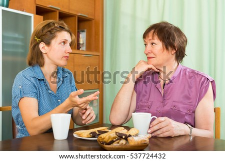 Young girl and her elderly mother having tea-drinking at the table and talking
