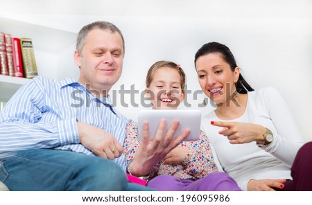 Young girl and her parents using a tablet - stock photo