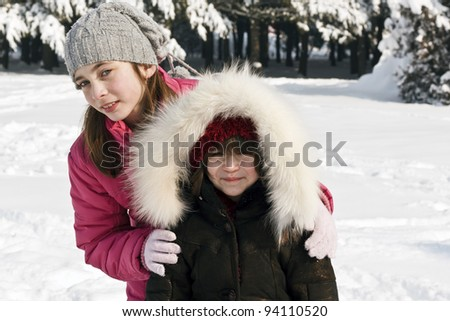 Young girl and her sister at winter day - stock photo
