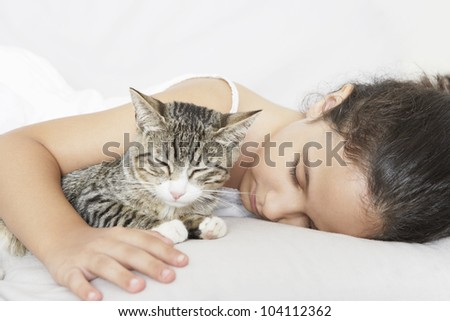 Young girl and kitten sleeping on a white sofa at home.