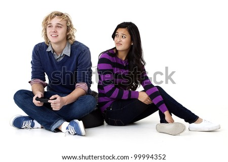 Young girl annoyed at her video game playing boyfriend - stock photo