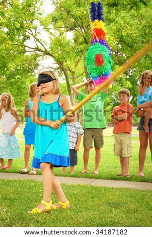 Young girl at an outdoor party hitting a pinata - stock photo