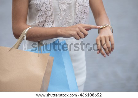 Young girl at shopping looking at the clock on hand. Bags, shopping, discounts , gray background, delay, time ,clock. Watch on female hand