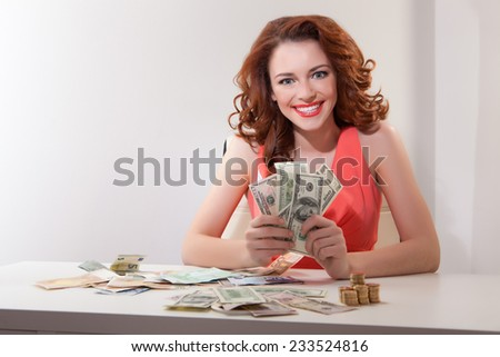 young girl at  table with greedy counts  money lying on  table and looking at  camera - stock photo