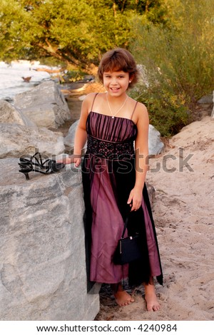 Young girl at the beach in formal attire.