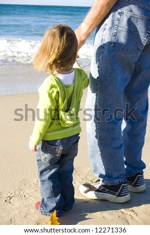young girl at the beach with her grandfather
