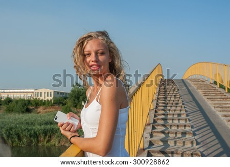 Young girl at the bridge with cellphone in hands - stock photo