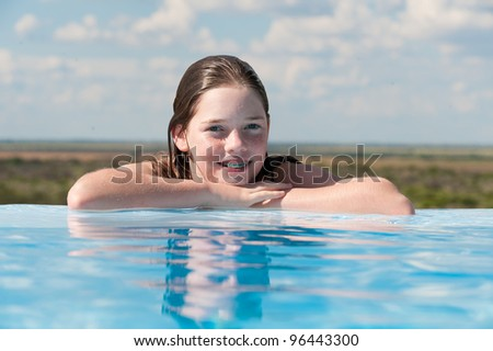 young girl at the edge of a pool - stock photo