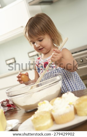 Young Girl Baking Cakes In Kitchen