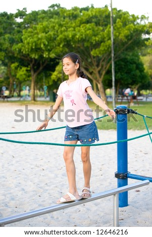 Young girl balancing on metal beam in playground activity - stock photo