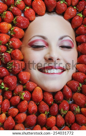 Young girl beauty face with red ripe fresh strawberries - stock photo