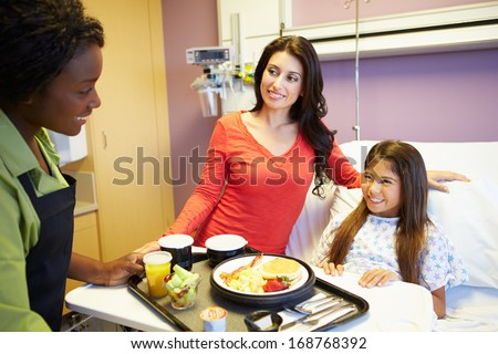 Young Girl Being Served Lunch In Hospital Bed - stock photo