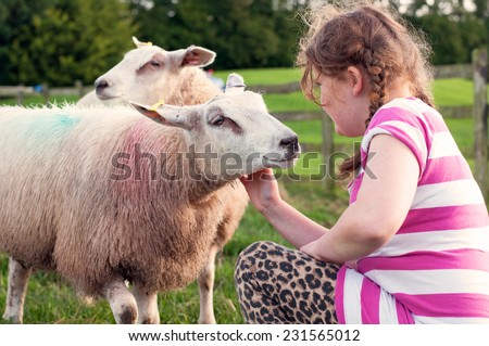 Young girl being sweet towards a friendly sheep - stock photo
