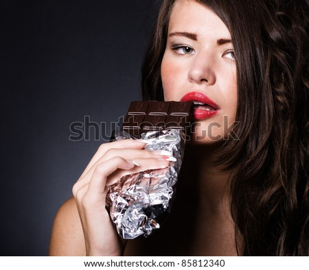 young girl biting a chocolate bar. - stock photo