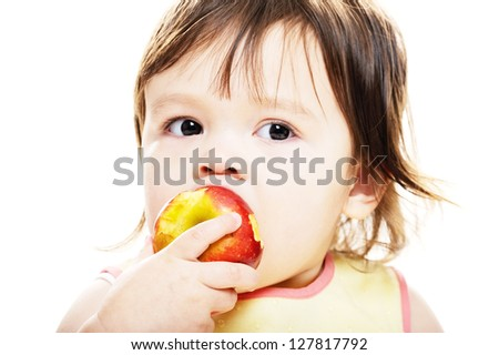 Young girl biting into red apple