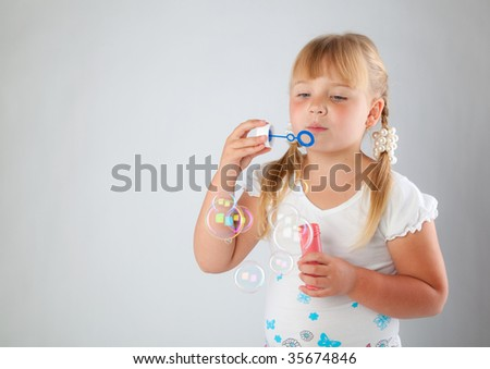 Young girl blow out soap bubbles on gray background