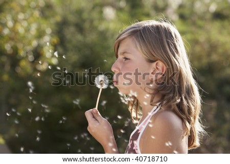 young girl blowing a dandelion and dreaming about the future