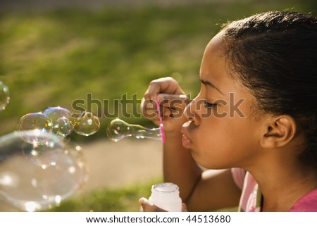 Young girl blowing bubbles outside. Horizontally framed shot. - stock photo