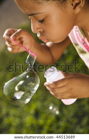 Young girl blowing bubbles outside. Vertically framed shot. - stock photo