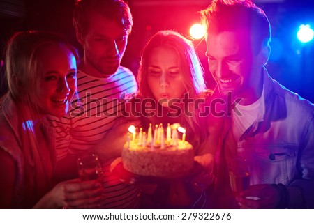 Young girl blowing candles on birthday cake between her friends - stock photo