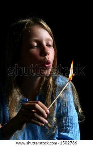 Young girl blowing match