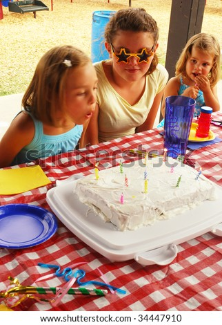 Young girl blowing out candles on her birthday cake - stock photo