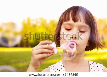 young girl blowing soap bubbles in a natural outdoor - stock photo