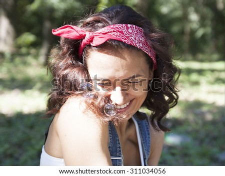 Young girl blowing soap bubbles outdoors