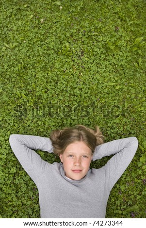 young girl (blue eyes, blonde) lying in the grass dreaming of ... - stock photo