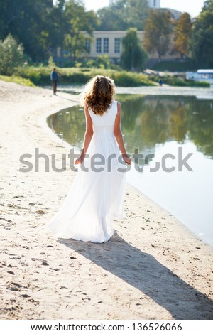 Young girl bride in a white dress walk the sunny coast of the river. Outdoor - stock photo