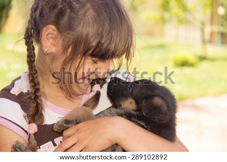 young girl, brunette, playing with puppies German shepherd on a lawn in the summer - stock photo