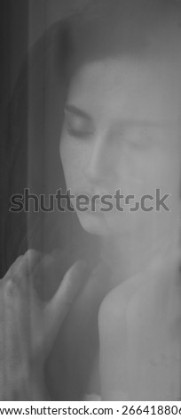 young girl by the window looking down, reflection of a beautiful girl in the window , black and white photo of beautiful girl reflected in the window in the room - stock photo
