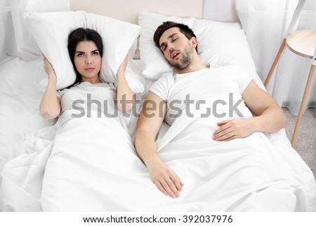 Young girl can't sleep because of her man's snoring. - stock photo