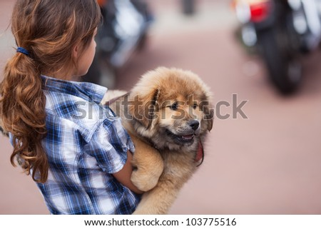 young girl carries an Elo puppy in her arms