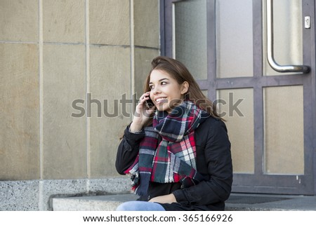 Young girl chatting on her mobile phone in town sitting in the entrance to a commercial building on the steps smiling in enjoyment as she listens to the conversation