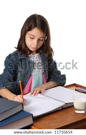 young girl / child writing in notebook at desk