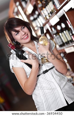 young girl chooses wine in a supermarket - stock photo