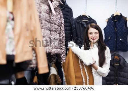 Young girl choosing jacket at clothing store - stock photo