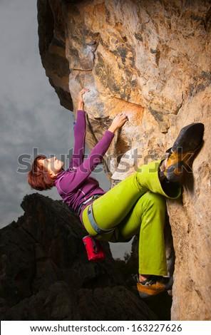 Young girl climbing on a limestone wall - stock photo
