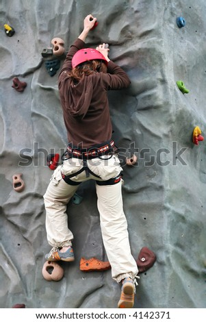 Young girl climbing to the rock climbing wall - stock photo