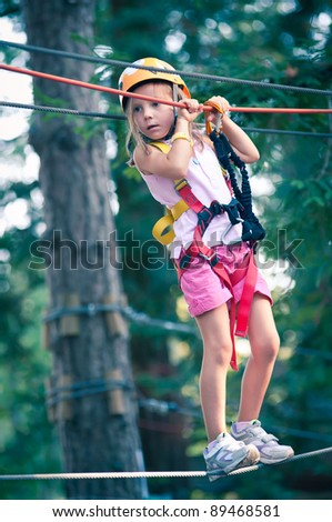 Young Girl climbing trees in Dolomites, Italy.