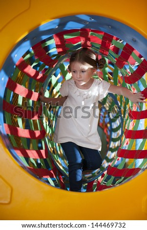 Young girl climbs through netted tunnel in soft play center - stock photo