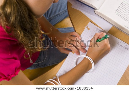 young girl concentrating on work at school desk writing