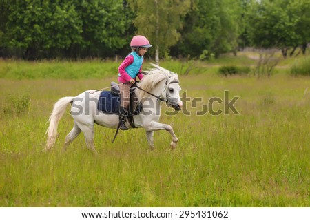 Young girl confident galloping horse on the field - stock photo