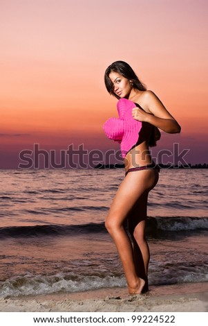 Young girl covered with pink hat stands on sunrise beach at dramatic dawn - stock photo