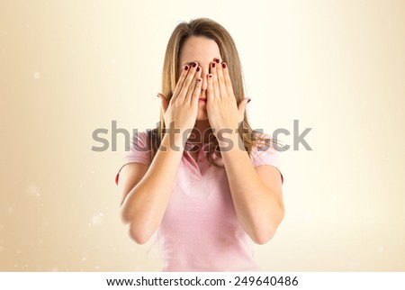 young girl covering her eyes over ocher background  - stock photo