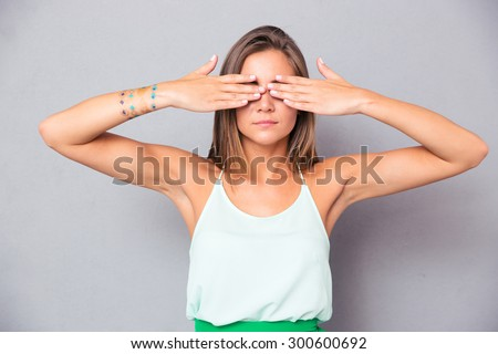 Young girl covering her eyes with hands over gray background - stock photo