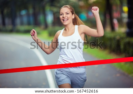 Young girl crosses finish line - stock photo