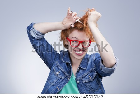 young girl cut hair with scissors with mad eyes. Bad day at the hairdresser.Studio shot. Gray background - stock photo