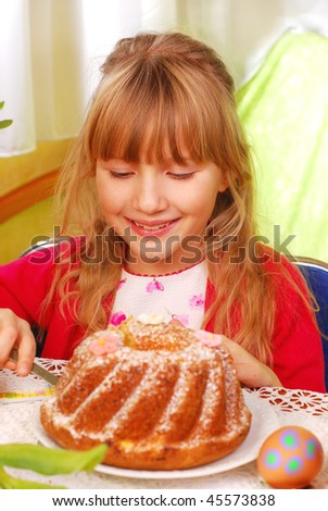 young girl cutting easter ring cake